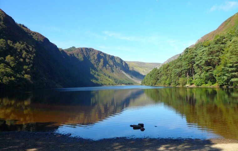 Glendalough upper lake on a beautiful day surrounded by green trees, hilltops and blue sky