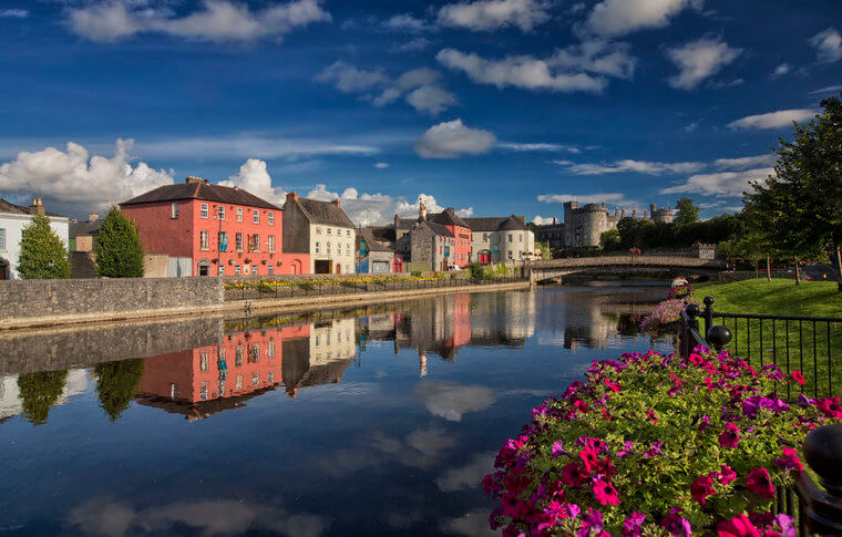 The bank of Kilkenny's river Nore, pretty pink flowers and pink coloured houses with castle in the back