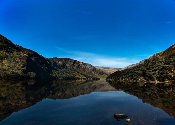 Glacial waters of Glendalough upper lake reflecting the surrounding trees and mountains