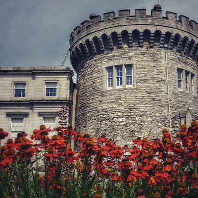 the beautiful round tower of Dublin Castle with a bed of dark red flowers in front