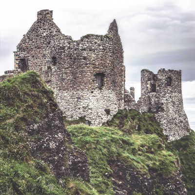 The grey ruins of Dunluce Castle perched cliffside