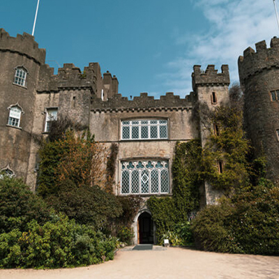 View of Malahide castle from the front, large stain-glass windows and old timey turrets