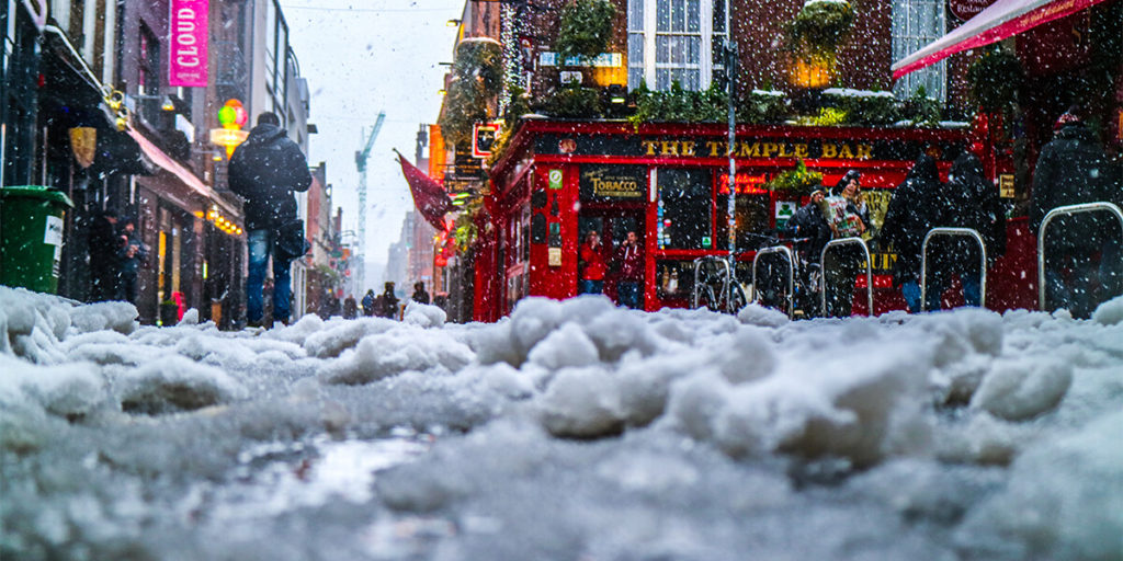 Dublin city centre sprinkled with snow with a red pub in the background